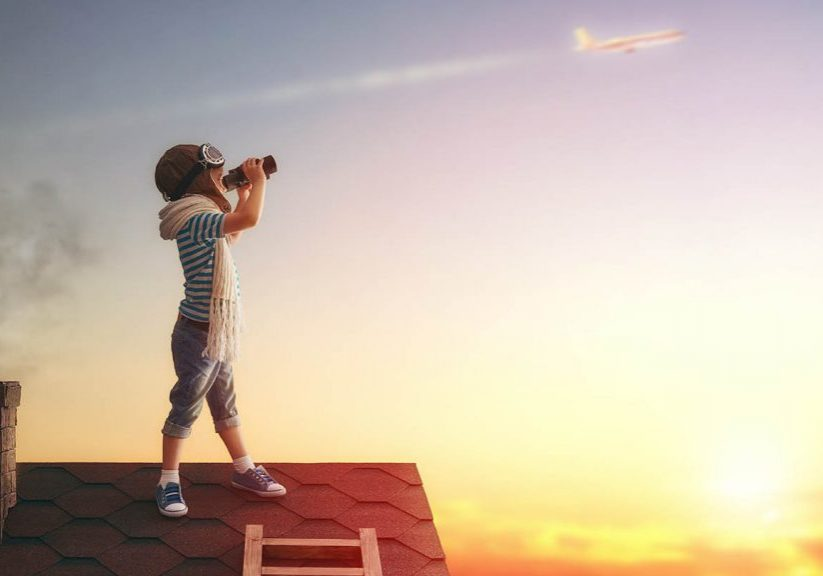 Cute little child playing on the roof of the house and looking at the sky and dreaming of becoming a pilots.